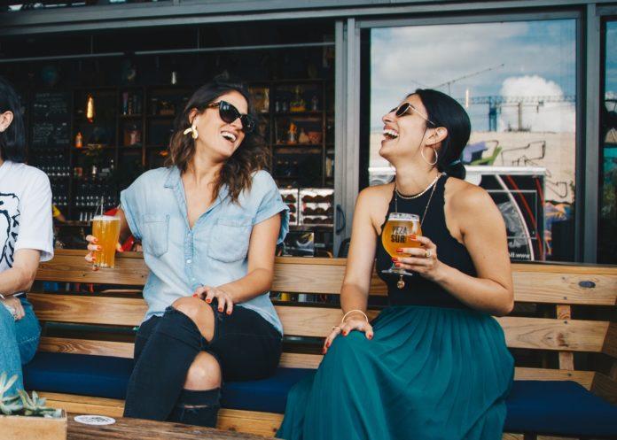 To kvinder griner sammen med øl