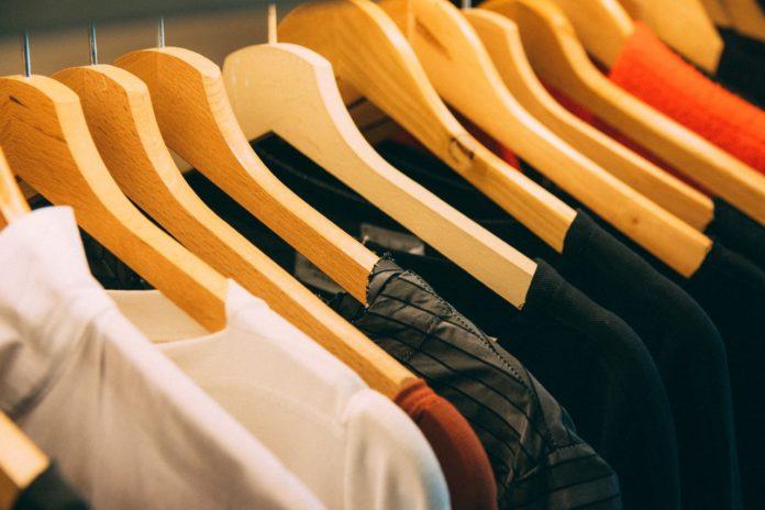 Tøj hænger på knage i forskellige farver