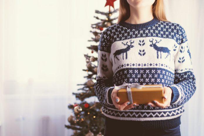 Pige har julesweater på og giver gave