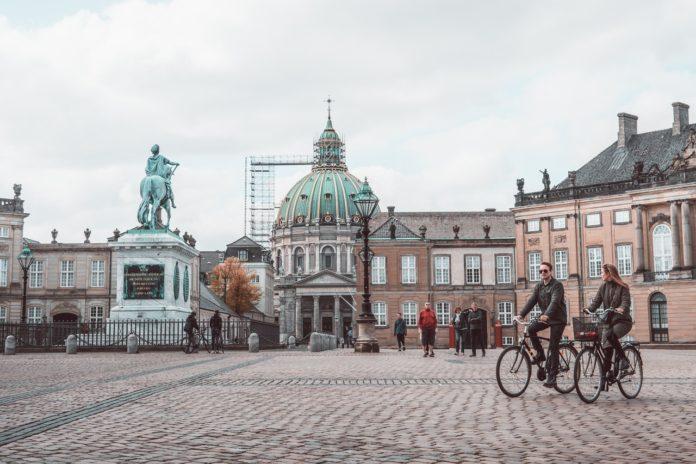 Person cykler forbi statue inde i københavn