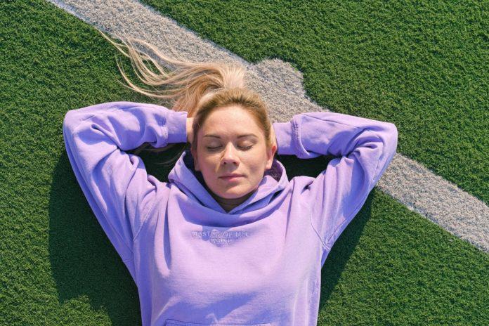 Dame ligger på græsplæne